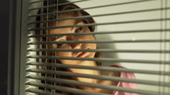 Sad woman looking through window at home Stock Footage