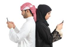 Arab couple addicted to smart phone - stock photo