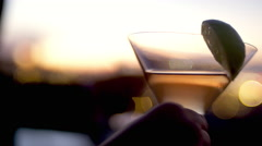 Close up of hands holding cocktails on a roof at dusk Stock Footage
