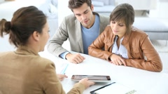 young couple in real estate agency signing property agreement - stock footage
