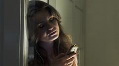 Melancholic woman listening music next to the window Stock Footage
