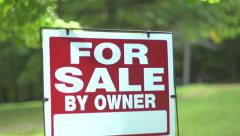 Dolly reveal to For Sale by Owner sign swaying in wind Stock Footage