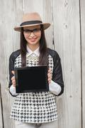 Pretty hipster showing tablet pc - stock photo