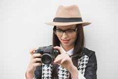 Pretty hipster looking at her camera - stock photo