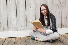 Pretty hipster reading a book - stock photo