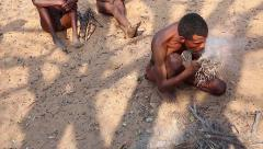 San Bushmen tribal men starting a fire with sticks and tinder. Stock Footage
