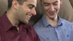 Two gay men, in close-up, looking at phones Stock Footage