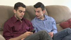 Two gay men talk, while one is on his phone. Stock Footage
