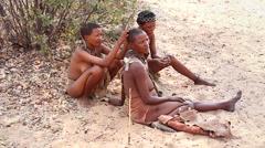 San Bushmen women groom each other and sharpen arrowhead in village. Stock Footage