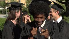 Stock Video Footage of A black graduation student points excitedly at camera - slow motion
