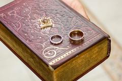 wedding rings on a gospel - stock photo
