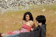 Teen couple sitting in grass outdoors together Stock Photos