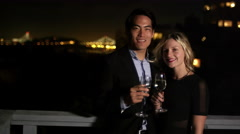 A couple stands on a roof holding wine glasses and smiles at the camera at night Stock Footage