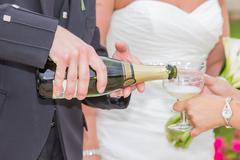Groom pooring champagne on a glass Stock Photos