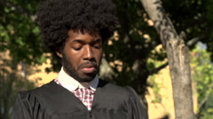Black student tries to fit a mortarboard on his afro. Stock Footage