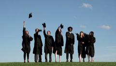 Racially-diverse students throw mortarboards - wide - slow motion Stock Footage