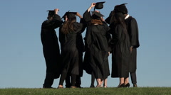 A circle of racially-diverse students throw mortarboards - slow motion - stock footage