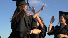 University students in academic caps and gowns celebrate their graduation Stock Footage