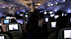 Airplane cabin interior with tv screens, passengers seated flying toward LAX Stock Footage