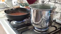 Pots on fire cooking italian pasta and tomatoes salsa Stock Footage