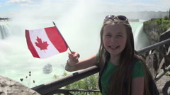 A girl waves a Canadian flag at Niagara Falls - slow motion - stock footage