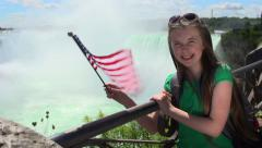 A girl waves a US flag at Niagara Falls. Stock Footage