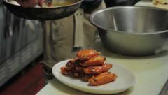 Chef places wings on plate - close-up shot Stock Footage