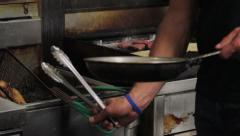 Chef preparing various foods with fryer and grill Stock Footage