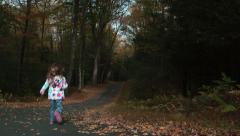 Young girl runs down a leaf-covered road Stock Footage