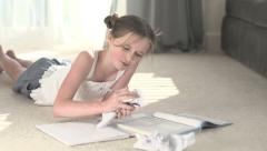 A young girl writes, tears out paper, starts again. - stock footage