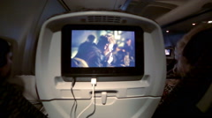 Airplane cabin with tv screens, passengers seated flying watching movie Stock Footage