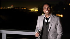 A man in a suit with a wine glass in his hand stands in front of the railing of Stock Footage