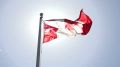 A sunlit Canadian flag flies in slow motion. Stock Footage