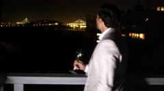 A man in a suit with a glass in his hand stands in front of the railing of a Stock Footage