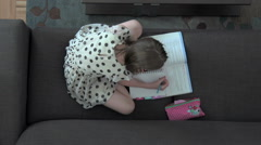 An overhead shot of a young girl doing homework - stock footage