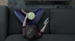 An overhead shot of a young girl watching TV. - stock footage