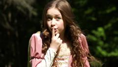 A princess puts her finger to her lips, sharing a secret outside in nature Stock Footage