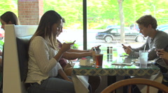 Friends use their cell phones at the dinner table. Stock Footage
