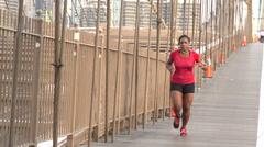 Black woman jogging over bridge Stock Footage