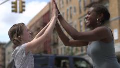 A white tween girl and a black woman high five in excitement Stock Footage