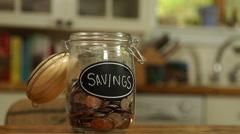 Loose change put in a saving jar Stock Footage