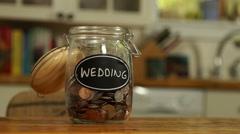 Loose change put in a saving jar, reading Wedding - stock footage