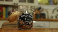 Loose change put in a saving jar, reading Hospital Bill Stock Footage