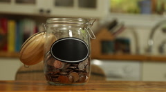 Loose change put in a saving jar, with blank label Stock Footage