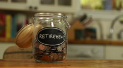 Loose change put in a saving jar, reading Retirement - stock footage
