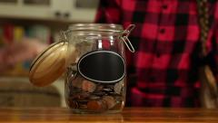 A child puts coins into her savings jar Stock Footage