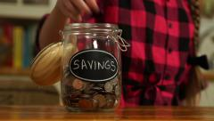 A child puts coins into her savings jar - stock footage