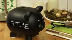 "Putting coins into a black piggy bank with ""Future"" written on it Stock Footage"