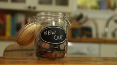 Loose change put in a saving jar, reading New Car Stock Footage