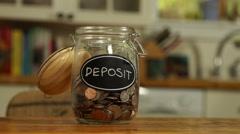 Loose change put in a saving jar, reading Deposit - stock footage